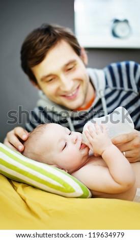 Portrait Of Father Feeding Newborn Baby (soft focus on eyes of baby) - stock photo