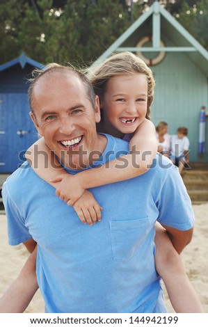 Portrait of father giving daughter piggyback ride on beach - stock photo