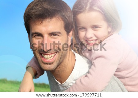 Portrait of father giving piggyback ride to daughter - stock photo