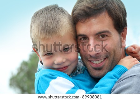 Portrait of father holding child in arms - stock photo