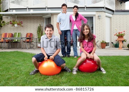 Portrait of father mother and kids in their backyard - stock photo