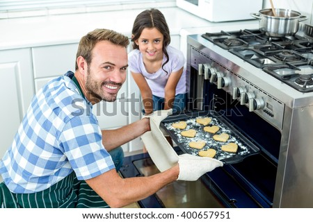 Portrait of father placing cookies tray in oven while daughter standing by him - stock photo