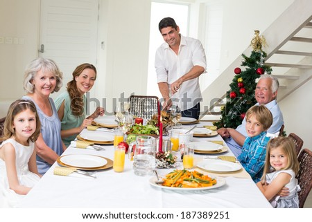 Portrait of father serving Christmas meal to family at dining table - stock photo