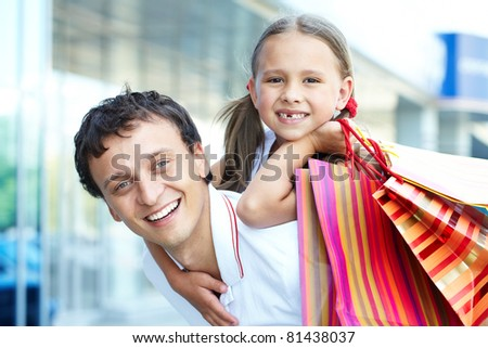 Portrait of father with daughter and shopping bags on back - stock photo