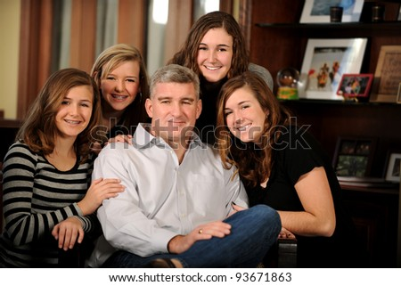 Portrait of father with his daughters indoors - stock photo