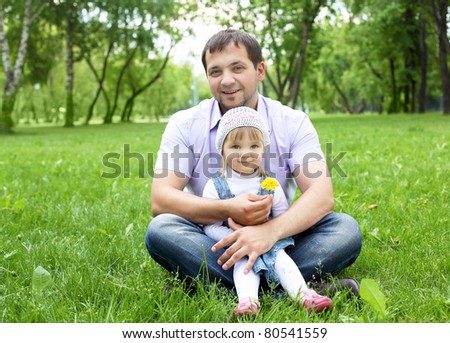 Portrait of father with little daughter outdoor in summer park