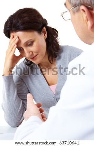 Portrait of fatigue female touching her head while man saying something to her - stock photo