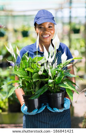 portrait of female african florist holding to potted plants - stock photo
