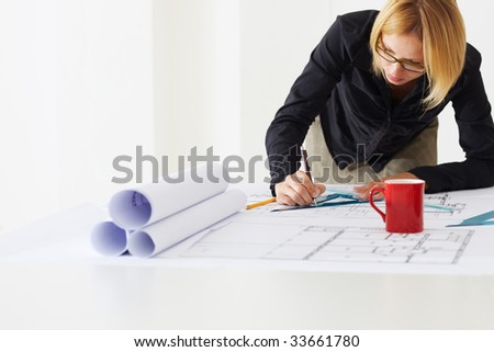 portrait of female architect drawing line on blueprint. Copy space - stock photo