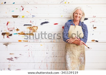 Portrait Of Female Artist Against Paint Covered Wall - stock photo
