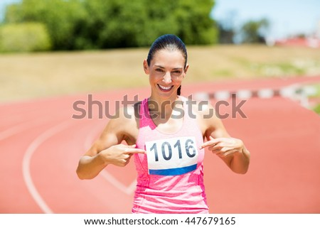 Portrait of female athlete pointing at badge on running track - stock photo