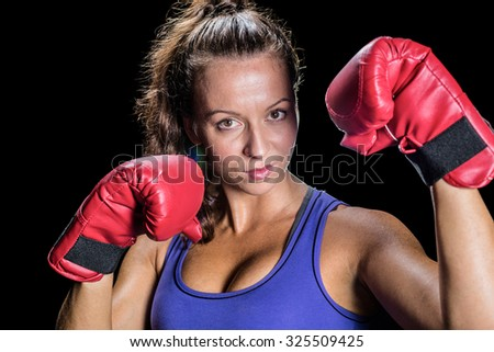 Portrait of female athlete with red gloves against black background