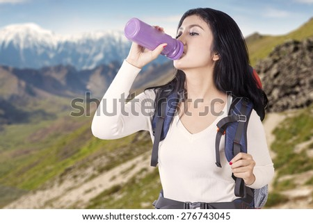 Portrait of female backpacker drinks fresh water from the bottle while carrying backpack on the edge of mountain - stock photo