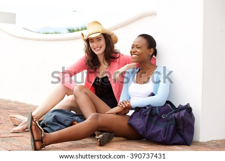 Portrait of female best friends waiting for train at railroad station platform - stock photo