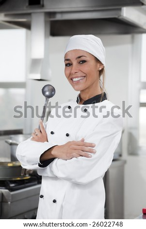 portrait of female chef looking at camera in kitchen - stock photo