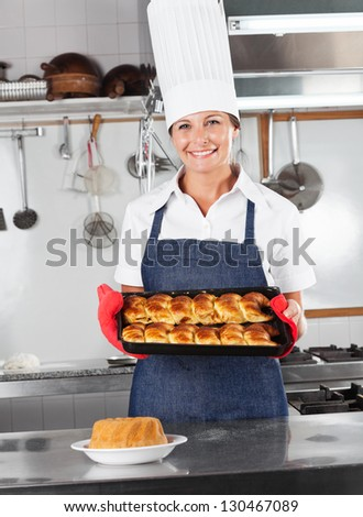 Portrait of female chef presenting baked breads in commercial kitchen - stock photo