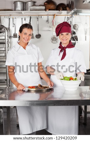 Portrait of female chefs with dishes standing at kitchen counter - stock photo