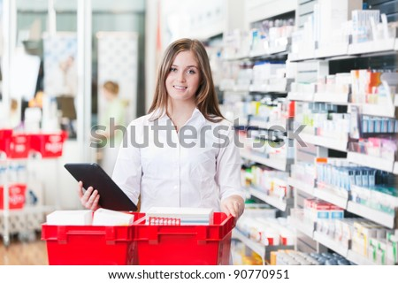 Portrait of female chemist holding tablet PC standing with basket at drugstore - stock photo