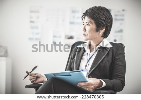 Portrait of female chief sitting in her office - stock photo