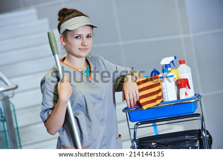 portrait of female cleaner in uniform with mop and cleaning equipment - stock photo