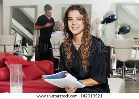Portrait of female client holding magazine with hairdresser working in the background at hair salon - stock photo
