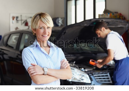 portrait of female client with arms folded in auto repair shop. - stock photo