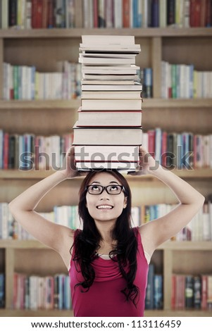 Portrait of female college student carrying a pile of books over her head. shot in library - stock photo