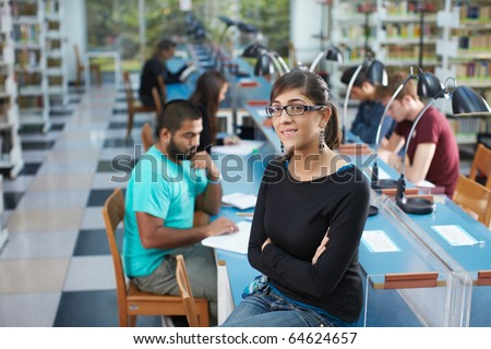 portrait of female college student sitting on table in library and looking at camera. Horizontal shape, waist up