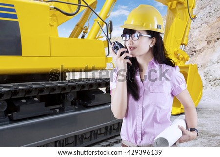 Portrait of female contractor talking on the walkie talkie with an excavator in the construction site - stock photo