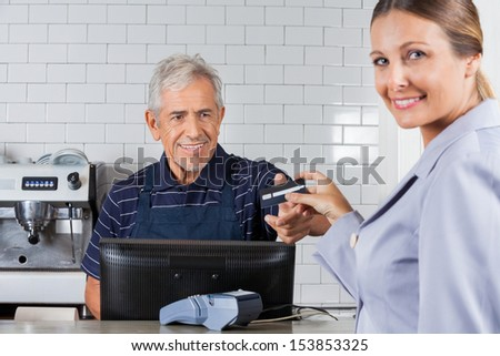 Portrait of female customer giving credit card to senior cashier in supermarket - stock photo