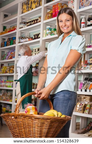 Portrait of female customer holding shopping basket with salesman in background - stock photo