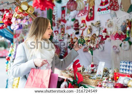 Portrait of female customer near counter with Christmas gifts in December