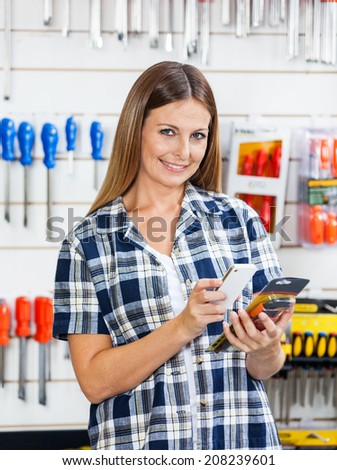 Portrait of female customer scanning product's barcode through mobilephone in hardware store - stock photo