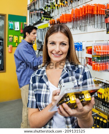 Portrait of female customer scanning product through mobile phone with man in background at hardware store - stock photo