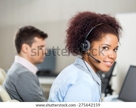 Portrait of female customer service representative wearing headset while colleague sitting in background at office desk - stock photo