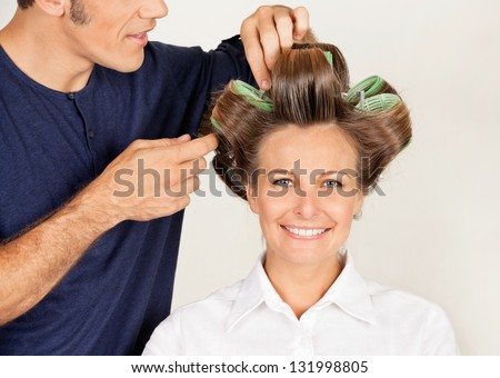 Portrait of female customer with hairstylist curling her hair at parlor - stock photo