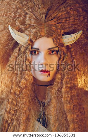Portrait of female demon with bloody lips, wearing scary contact lenses - stock photo