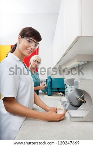 Portrait of female dentist holding dental plaster mold with assistant at clinic - stock photo