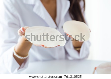Portrait of female doctor choosing mammary prosthesis in the office.