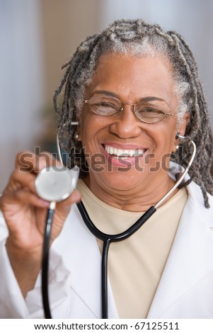 Portrait of female doctor holding stethoscope up - stock photo