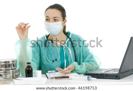 Portrait of female doctor in protective green uniform and medical mask with drug an laptop at office - stock photo