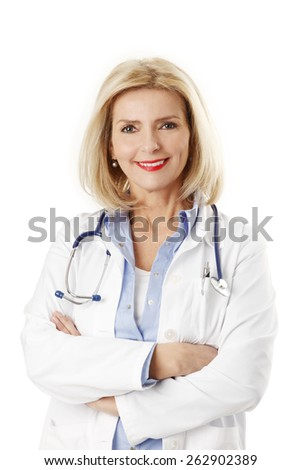 Portrait of female doctor standing against white background while looking at camera and smiling.  - stock photo