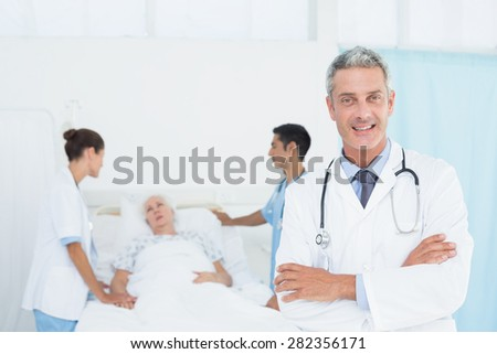Portrait of female doctor with colleagues and patient behind - stock photo
