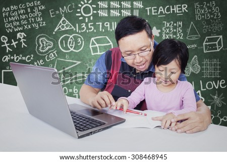 Portrait of female elementary school student studying in the classroom with her teacher, using a book and laptop on the table - stock photo