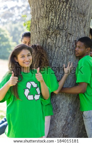 Portrait of female environmentalist gesturing thumbs up with friends hugging tree in background - stock photo