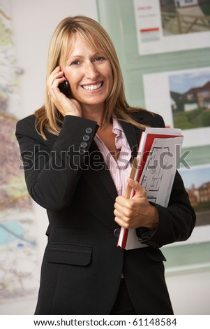 Portrait Of Female Estate Agent In Office On Phone - stock photo