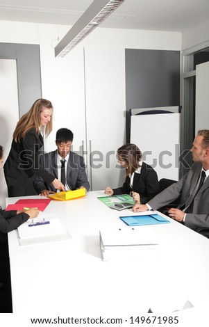 Portrait of female executive discussing with male associates in office - stock photo