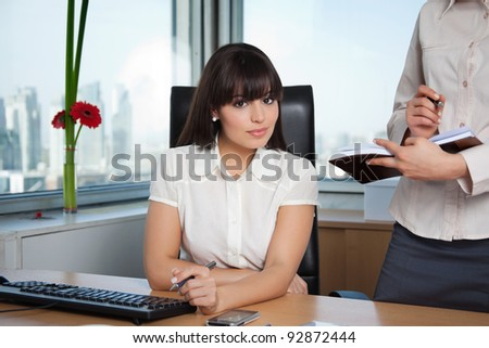 Portrait of female executive smiling with colleague standing beside her with calender - stock photo