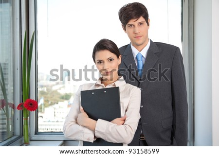 Portrait of female executive standing with male executive - stock photo