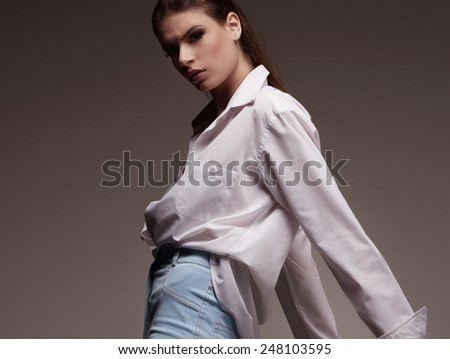 Portrait of Female fashion model with serious face in white man shirt